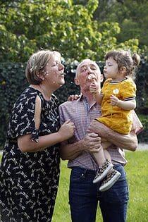 grootouders en kleinkind blazen paardenbloempluisjes