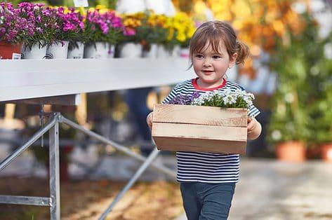 Dag van het Gezin - meisje met bloembak - Gezinsbond zet initiatieven in de bloemetjes