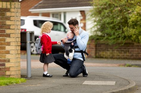 Man taking his daughter to school. He kneels down, holding a mobile telephone to his ear he tries to pacify his baby son with a dummy. The baby is in a harness on his chest.