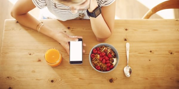 Directly above shot of young female hipster using smart phone. Orange juice and bowl of granola are kept on wooden table. Woman is holding mobile phone with blank screen.