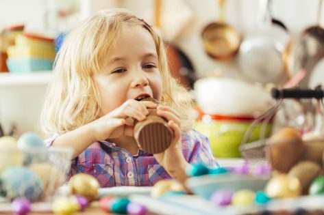 Cute little girl eating chocolate Easter bunny.